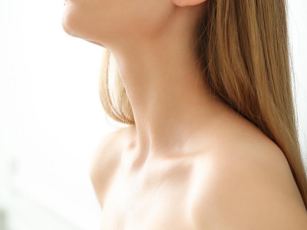 Close do colo e do pescoço de uma mulher. Representação de como cuidar da pele do colo e do pescoço.