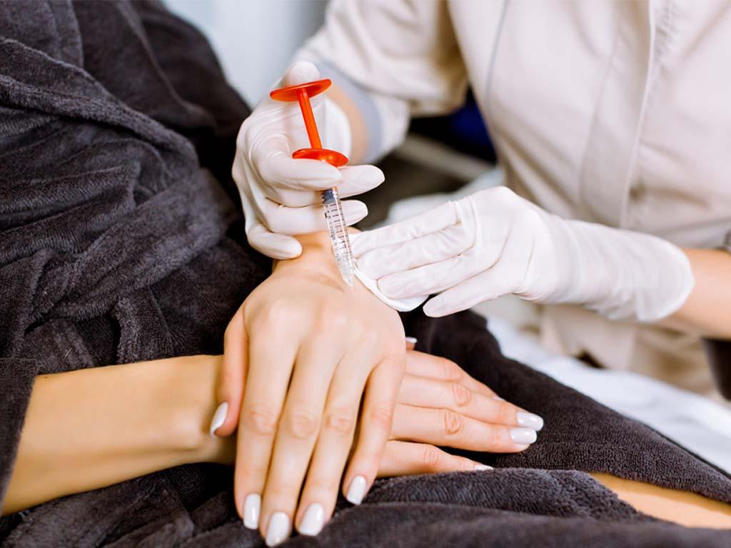 Dermatologista aplicando preenchimento dérmico na mão de uma mulher com o intuito de rejuvenescer as mãos dela.
